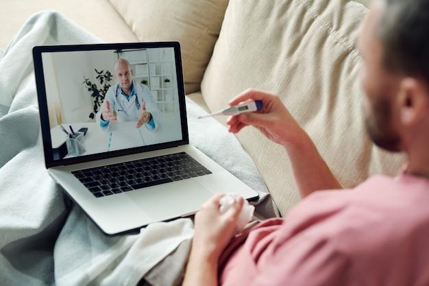 Uomo malato con laptop e fazzoletto accartocciato seduto sul divano sotto la coperta mentre guarda il termometro e consulta un medico online