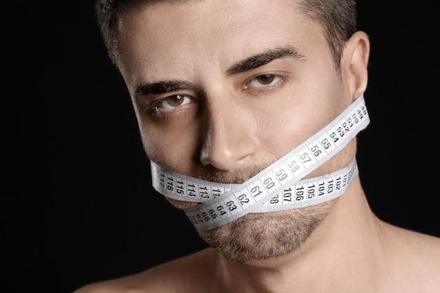 Uomo malato con nastro di misurazione su sfondo scuro. concetto di anoressia