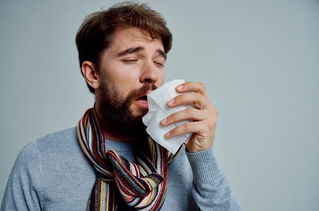 Uomo malato con una sciarpa intorno al collo problemi di salute influenza sfondo chiaro. foto di alta qualità