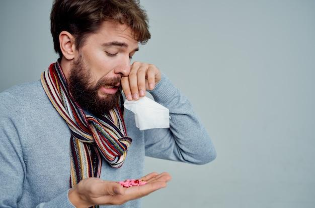 Uomo malato con una sciarpa intorno al collo problemi di salute influenza sfondo chiaro