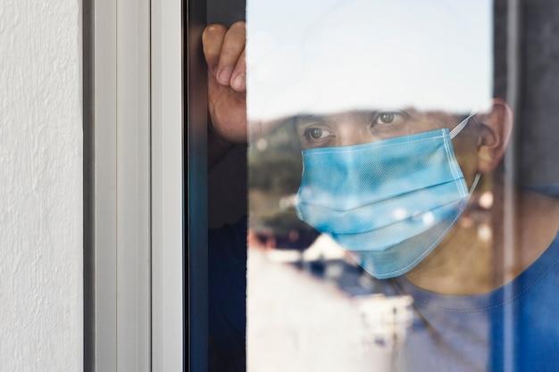 L'uomo malato con la mascherina chirurgica sta guardando il paesaggio attraverso la finestra