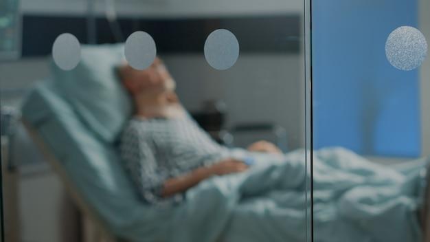 Uomo anziano malato che giace nel letto del reparto ospedaliero con collare cervicale