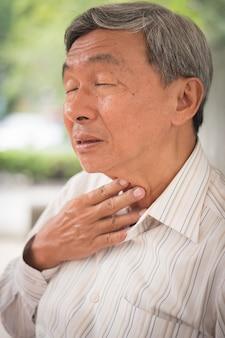 Vecchio malato con mal di gola a causa di raffreddore o influenza, sintomo di infezione da coronavirus da covid-19