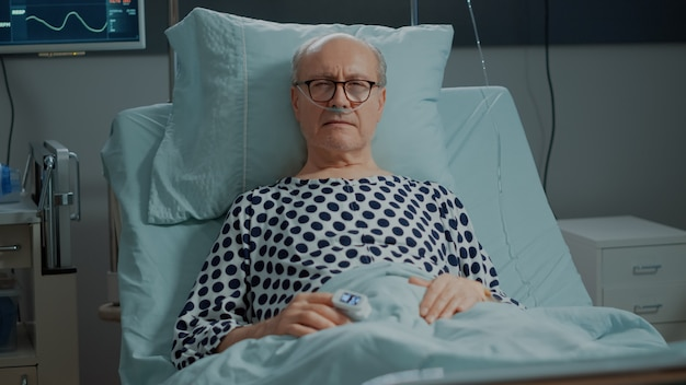 Paziente anziano malato nel letto del reparto ospedaliero con tubo di ossigeno nasale