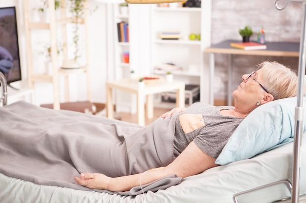 Anziana malata sdraiata nel letto della casa di cura. donna sola.