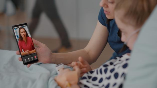 Paziente malato che riposa a letto con la madre che saluta un amico remoto durante la videochiamata online