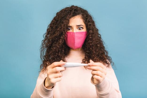 Giovane donna triste e malata, maschera medica sterile per proteggersi dal virus del coronavirus covid-19 durante la quarantena pandemica, con in mano un termometro