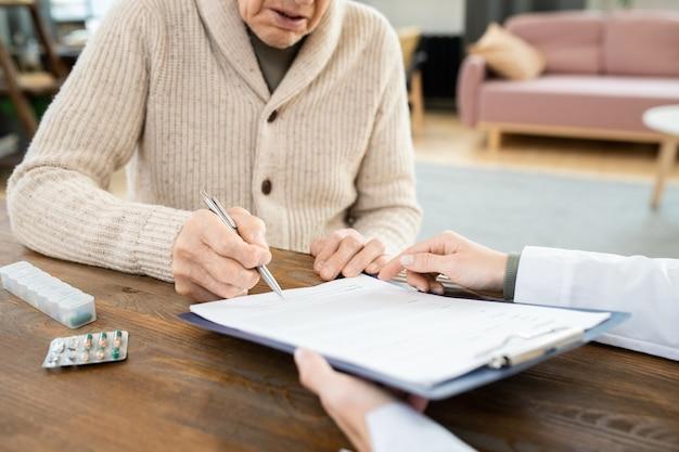 Uomo anziano malato in abbigliamento casual che firma un documento medico negli appunti mentre è seduto al tavolo di fronte alla dottoressa che indica la carta