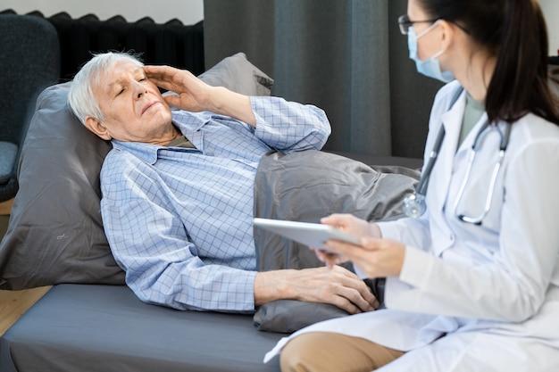 Uomo anziano malato che tocca la testa mentre è sdraiato sul divano sotto la coperta e spiega i suoi sintomi al medico di base durante la sua visita