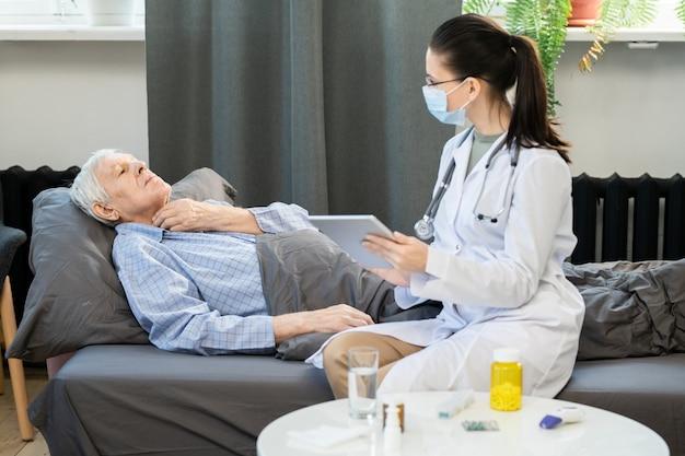 Uomo anziano malato che si tocca la gola mentre è sdraiato sul divano sotto la coperta e mostra al giovane medico generico dove fa male durante la sua visita