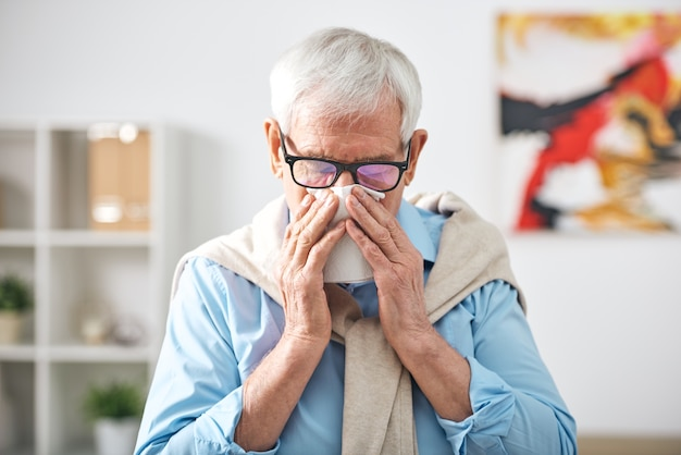 Uomo anziano in pensione malato con il fazzoletto dal naso stare a casa mentre si sente male durante l'epidemia di influenza