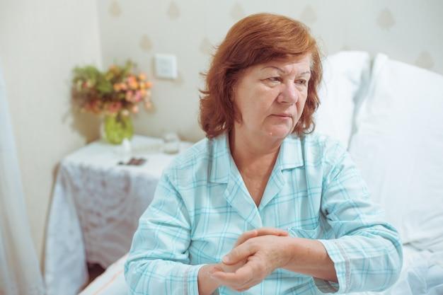Donna anziana malata a letto nei suoi appartamenti che le prende il polso alla mano