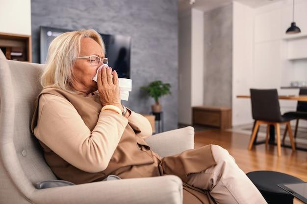 Donna maggiore ammalata che si siede nella sedia a casa e che soffia il naso.
