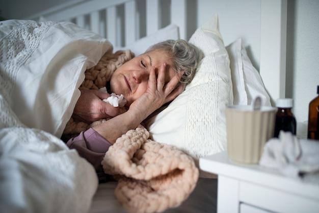 Una donna anziana malata che dorme nel letto di casa, raffreddore e influenza