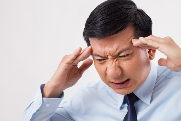 Uomo malato, stressato, oberato di lavoro con mal di testa, emicrania, vertigini, sbornia