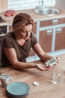 Malato e stanco. donna bionda malata e stanca che prende pillole antidepressive in cucina