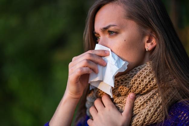 Donna infelice malata in sciarpa lavorata a maglia ha preso un raffreddore in autunno e soffre di naso chiuso e che cola e usa un tovagliolo di carta durante gli starnuti all'aperto
