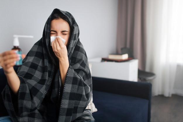 Spruzzo della gola della stretta della giovane donna ammalata e infelice. si copre il naso di tessuto bianco. modello molto malato. si copre la testa con una coperta.
