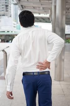Uomo asiatico malsano malato che soffre di mal di schiena, problemi alla colonna vertebrale, ernia del disco, dislocazione o spostamento del disco spinale, sindrome dell'ufficio