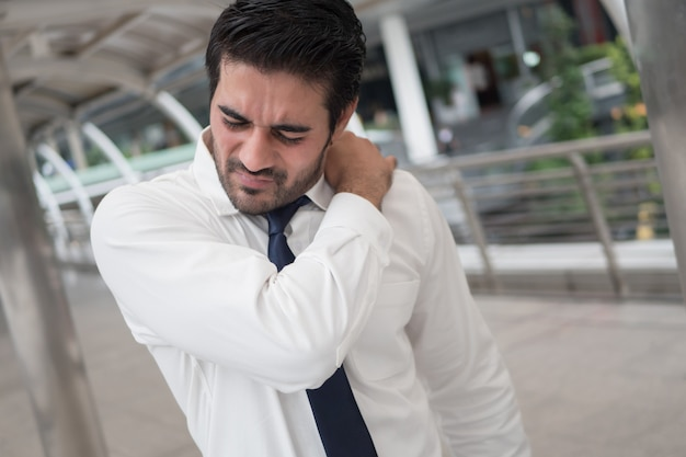 Uomo asiatico malato e malsano che soffre di dolore alla spalla, spalla rigida, artrite, gotta, sindrome dell'ufficio