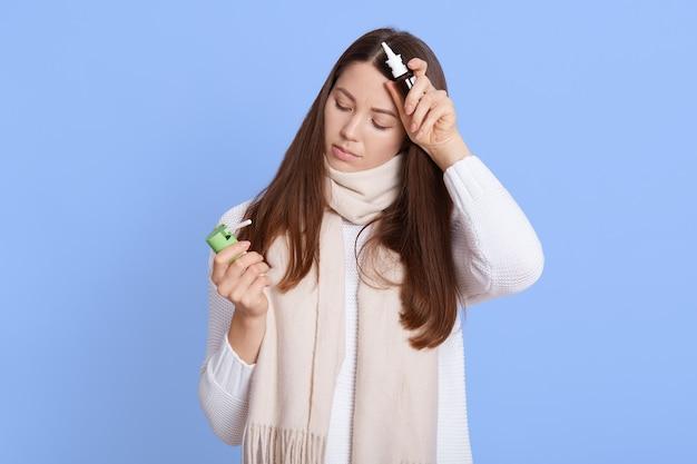 Donna europea sconvolta malata che indossa abbigliamento casual, tenendo in mano spray nasali e per la gola