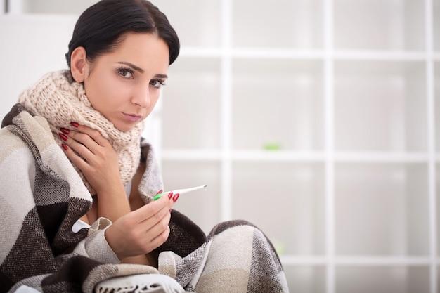 La donna malata a letto con il termometro ha la febbre ad alta temperatura
