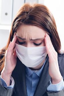Un uomo d'affari malato della donna in una mascherina medica protettiva lavora nell'ufficio. la ragazza stringe la testa per il dolore e preme le mani sulle tempie.