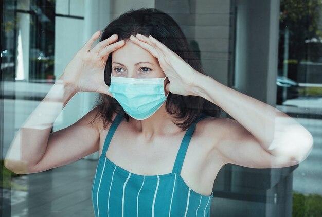 Donna malata di corona virus che guarda attraverso la finestra e indossa una maschera di protezione