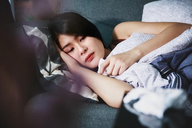 Donna malata coperta con una coperta sdraiata sul divano