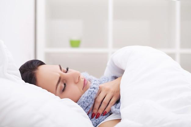 Donna malata. influenza. ragazza con il freddo sdraiato sotto una coperta che tiene un fazzoletto