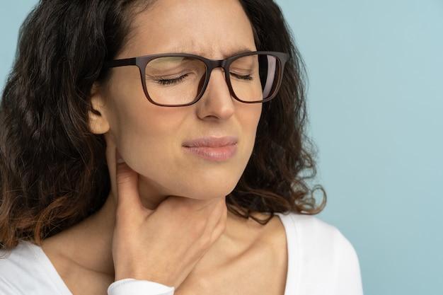 Donna malata con mal di gola, tonsillite, sofferenza di deglutizione dolorosa in studio