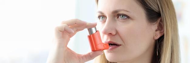 Donna malata che tiene inalatore di ormoni vicino al trattamento della bocca del concetto di asma bronchiale