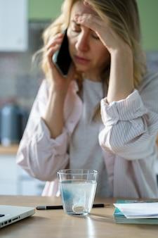 Donna malata che tiene il bicchiere di acqua frizzante con sciogliere la pillola di aspirina effervescente prendendo farmaci