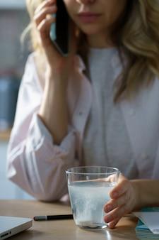 Donna malata che tiene in mano un bicchiere di acqua frizzante con una pillola di aspirina effervescente che si dissolve prendendo farmaci