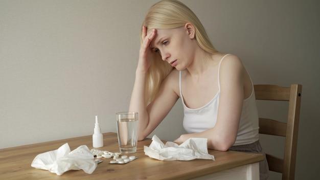 Una donna malata è seduta a un tavolo con un mucchio di medicine. una giovane donna si soffia il naso in un tovagliolo e soffre di un forte raffreddore. curare l'influenza a casa. 4k uhd
