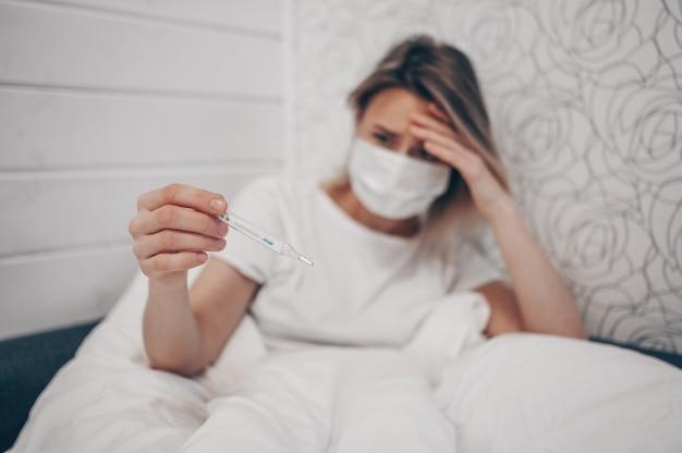 Donna malata che si trova a letto con il termometro e che controlla isolamento a quarantena ad alta temperatura a casa. corona virus covid-19. l'infezione provoca malattie respiratorie primi sintomi tosse febbre mal di testa