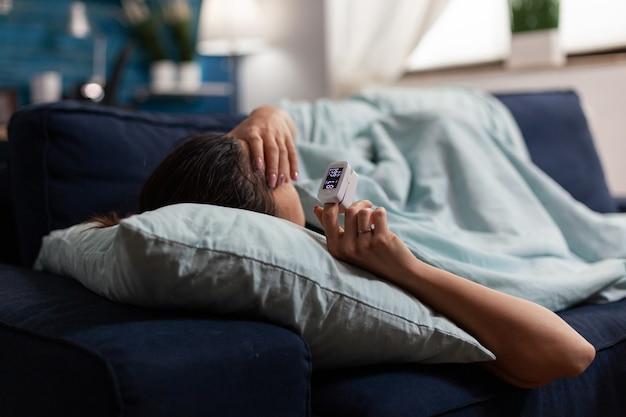 Donna malata sul divano che utilizza la tecnologia medica per il coronavirus pandemico
