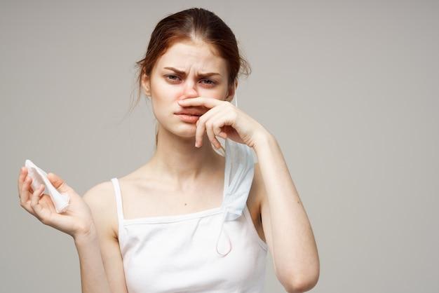 Donna malata in maglietta bianca con uno sfondo chiaro di sciarpa