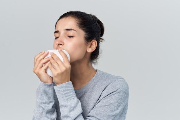 Donna malata che si pulisce il viso con un fazzoletto di infezione da influenza