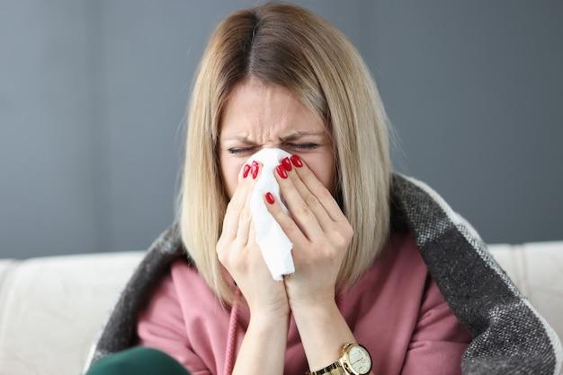 Donna malata pulendosi il naso con un tovagliolo di carta. concetto di epidemia di influenza