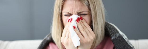 Donna malata che si pulisce il naso con il concetto di epidemia di influenza del tovagliolo di carta