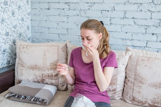 Una donna malata con il raffreddore guarda il termometro. temperatura molto alta e mal di testa