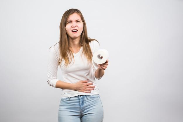 Donna malata con le mani che premono il suo addome inferiore del cavallo, tenendo il rotolo di carta. problemi medici