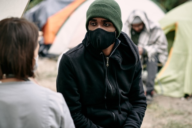 Malato giovane rifugiato nero con maschera facciale e cappello che parla con un'infermiera nel campo di migranti