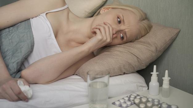 La giovane donna bionda ammalata giace a letto a casa sotto la coperta e controlla il termometro mentre si soffia il naso contro il fazzoletto di carta.