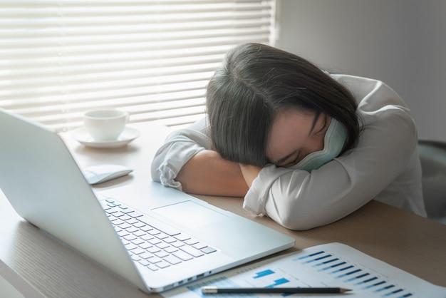 Maschera di protezione d'uso del giovane impiegato femminile malato che dorme sullo scrittorio con il computer portatile