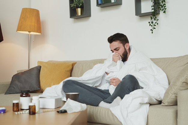 Giovane malato con influenza o coronavirus seduto sul divano in soggiorno mentre tossisce nella coperta durante l'autoisolamento a casa
