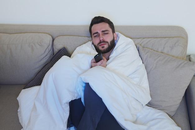 Giovane malato con telecomando seduto sul divano davanti al televisore e scegliendo il canale per guardare il film mentre si resta a casa con covid Foto Premium