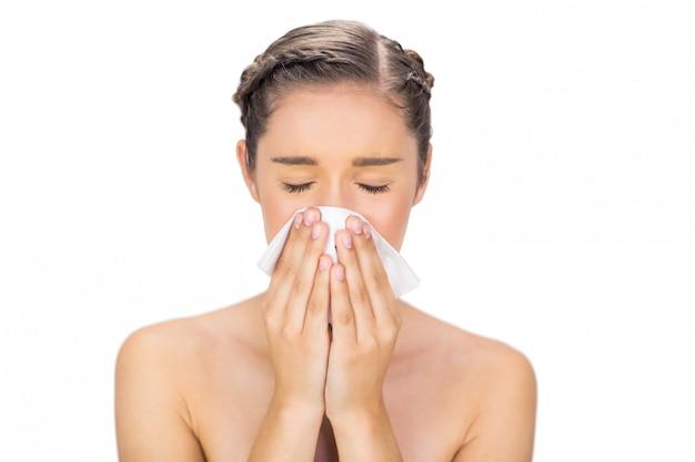 Modella giovane malata che soffia il naso