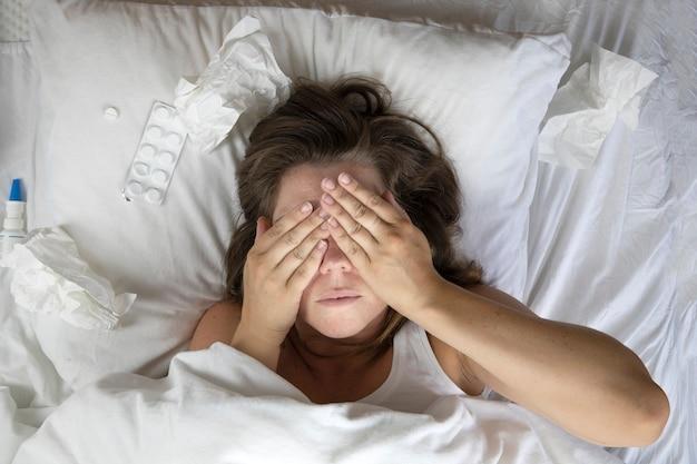 Una giovane donna malata a letto, sdraiata con la testa sotto le coperte e un mucchio di fazzoletti accanto a lei